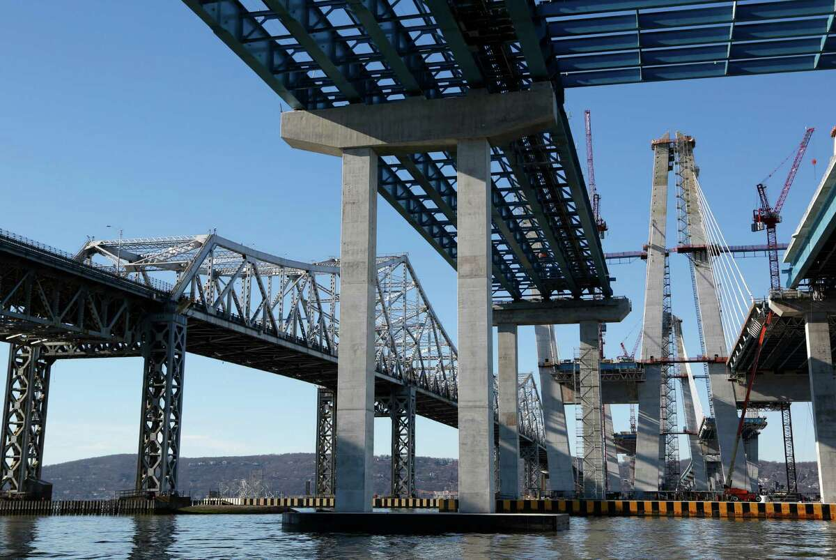 Work continues on the new Tappan Zee Bridge, right, while the older one, left, is still in use near Tarrytown, N.Y., Tuesday, Dec. 20, 2016. New York Gov. Andrew Cuomo said he made replacing the old Tappan Zee a priority because it was disintegrating and eating up hundreds of millions of dollars for basic repairs just to keep motorists safe. (AP Photo/Seth Wenig) ORG XMIT: NYSW107