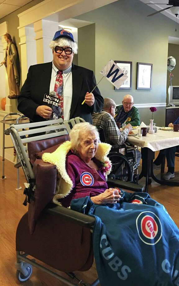 In this Nov. 4, 2016 photo provided by St. Mary's Home for the Aged at Felician Village, quality of life supervisor Tim Reinemann dresses like the late Cubs announcer Harry Caray as he leads the World Series celebration with 105-year-old resident Suzanne Sieben at Felician Village in Manitowoc, Wis. Sieben, who lived most of her life about a mile from Wrigley Field, close enough to hear the roar of the crowd if the wind was blowing just right, could remember with absolute clarity that the Cubs had won it all before she died on Dec. 5. (St. Mary's Home for the Aged at Felician Village via AP) ORG XMIT: CX103 / St. Mary's Home for the Aged a