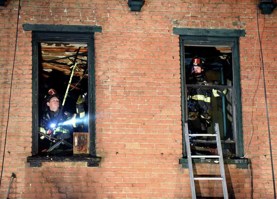 Albany firefighters work to completely extinguish fire at 284 Lark St., right, on Thursday, Dec. 22, 2016, Albany N.Y. (Cindy Schultz / Times Union) Photo: Cindy Schultz / Albany Times Union