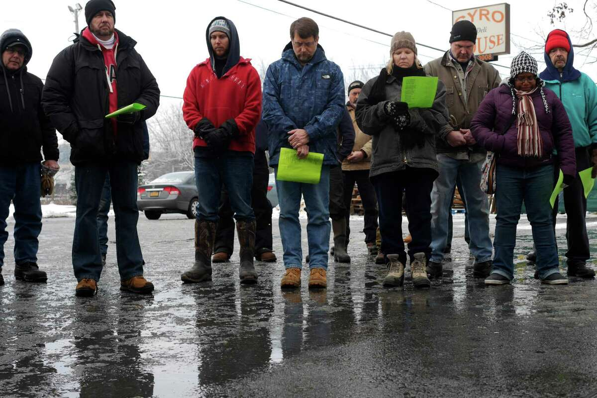 Striking Momentive workers and their supporters take part in a prayer during a religious service outside of Momentive Performance Materials on Thursday, Dec. 22, 2016, in Waterford, N.Y. Religious leaders from the Capital Region held the service to show support for the workers of Momentive who have been on strike for over seven weeks. (Paul Buckowski / Times Union)