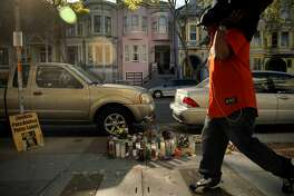 A pedestrian walks past a memorial to Amilcar Perez-Lopez at the scene on Folsom Street in San Francisco, Calif., on Wednesday, March 4, 2015, where Perez-Lopez was shot and killed by SFPD the previous Thursday. Questions remain from neighbors and other witnesses as to how police claim the shooting unfolded. Stray bullets from the officers gunfire hit the pink house across the street.
