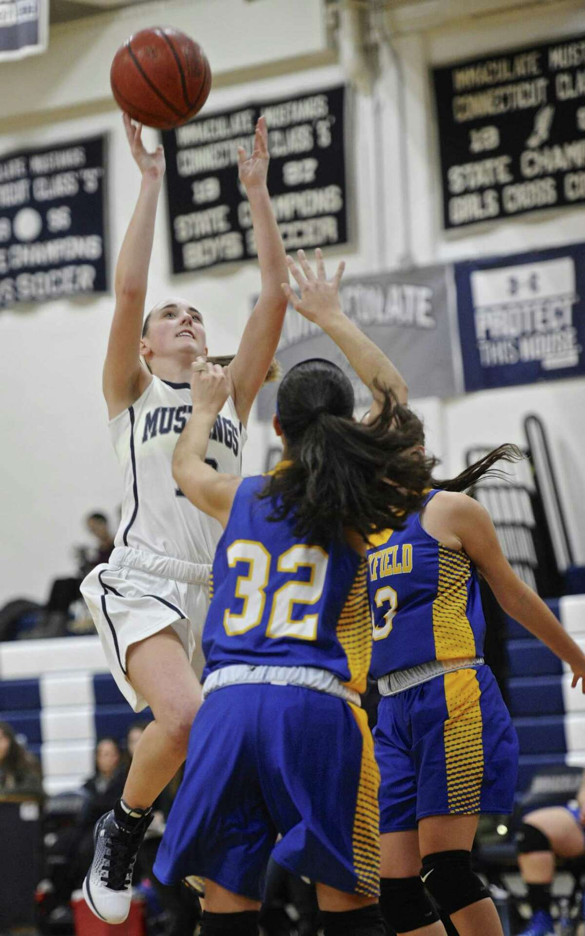 Immaculate's Meghan Schlichtig (10) goes to the basket over Brookfield's Jenna Joshi (32) in the girls high school basketball game between Brookfield and Immaculate high schools, on Thursday night, December 22, 2016, at Immaculate High School, Danbury, Conn.