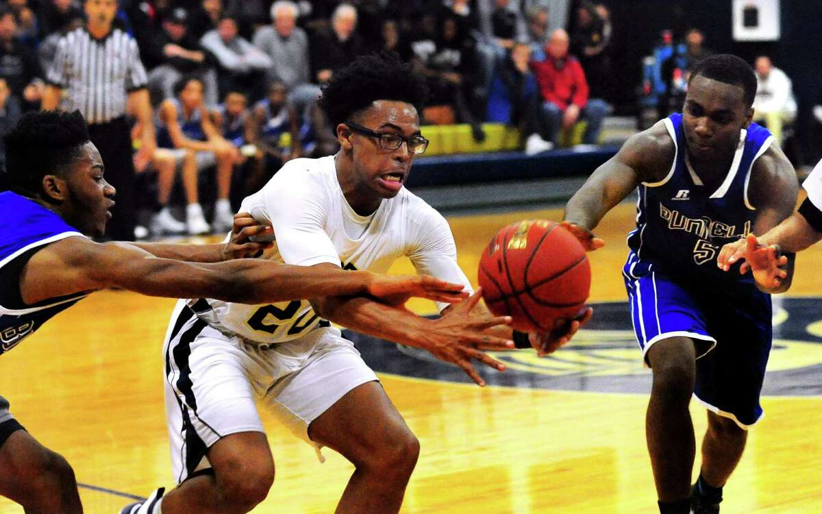 Notre Dame of Fairfield's Noreaga Davis, center, tries to take control of a rebound as Bunnell's Kwann Geer, left, and Armstrong Antoine, right, converge during boys basketball action against Bunnell in Fairfield, Conn., on Thursday Dec. 22, 2016.