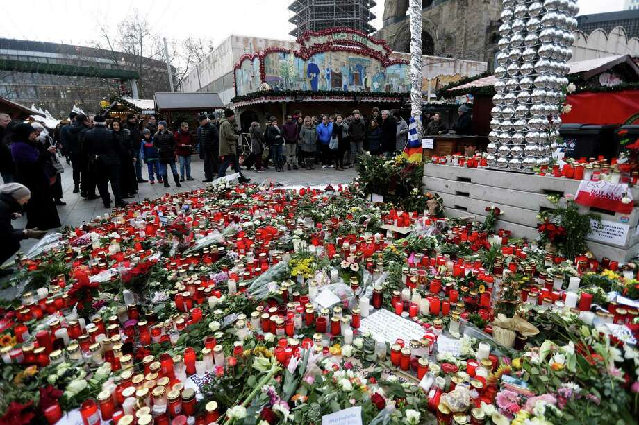 People stand around candles at the reopened Christmas market, three days after a truck ran into the crowd and killed several people, at the Kaiser Wilhelm Memorial Church in Berlin, Thursday, Dec. 22, 2016. (AP Photo/Markus Schreiber) ORG XMIT: MSC112 Photo: Markus Schreiber / Copyright 2016 The Associated Press. All rights reserved.