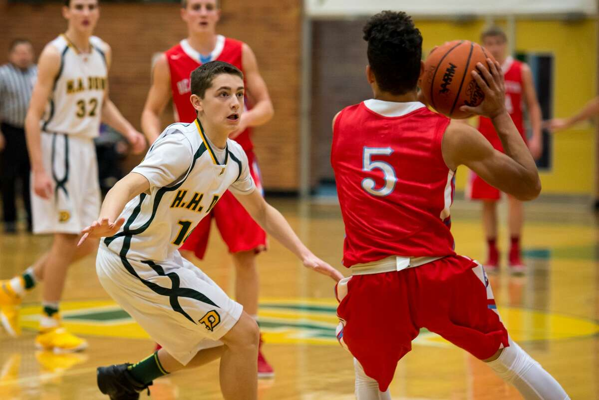 Dow's Mitchell Hayes defends Beaverton's Nate Taylor as Taylor looks to pass on Thursday at H. H. Dow High School.