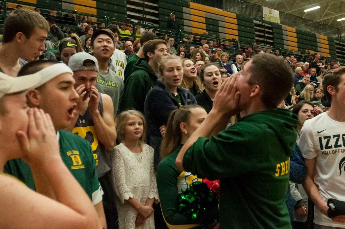 Dow senior Lucas M. Shelton chants during the boys varsity basketball game on Thursday at H. H. Dow High School.