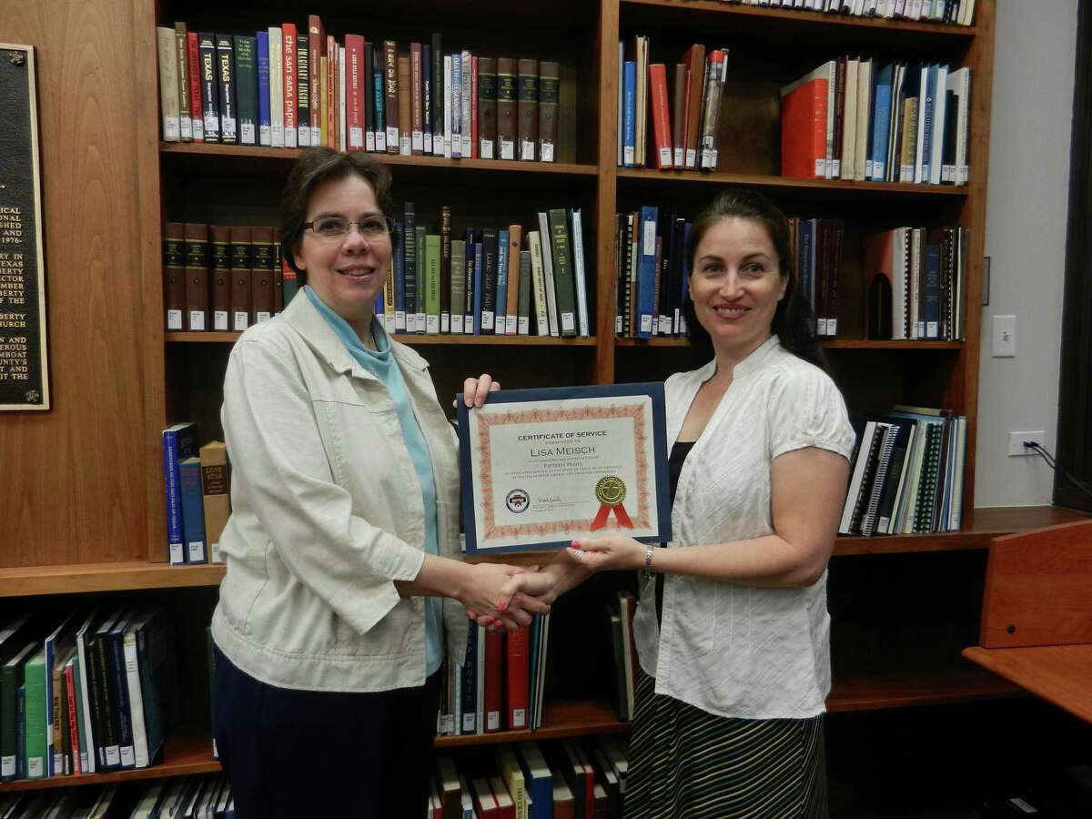Lisa Meisch (left) receives recognition of her 15 years of service from Sam Houston Center Manager Alana Inman.