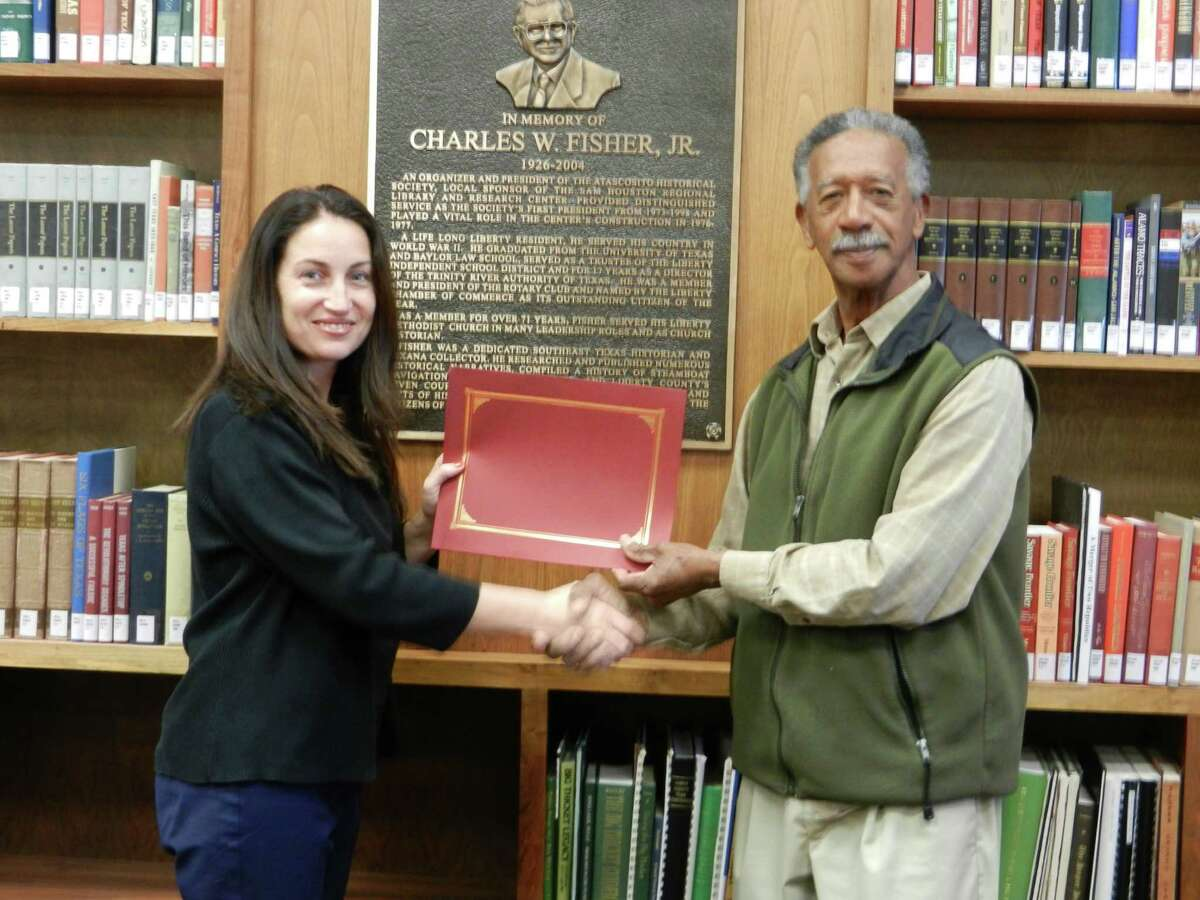 Sam Houston Center Manager Alana Inman presents recognition of his 10 years of service to Curtis Herman.