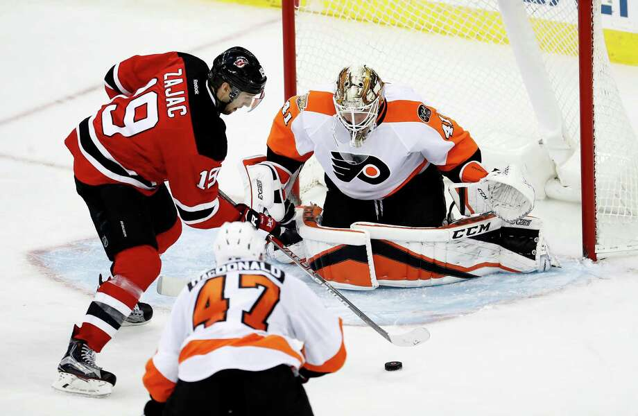 New Jersey Devils center Travis Zajac (19) attacks against Philadelphia Flyers goalie Anthony Stolarz (41) and defenseman Andrew MacDonald (47) during the third period of an NHL hockey game, Thursday, Dec. 22, 2016, in Newark, N.J. (AP Photo/Julio Cortez) ORG XMIT: NJJC110 Photo: Julio Cortez / Copyright 2016 The Associated Press. All rights reserved.