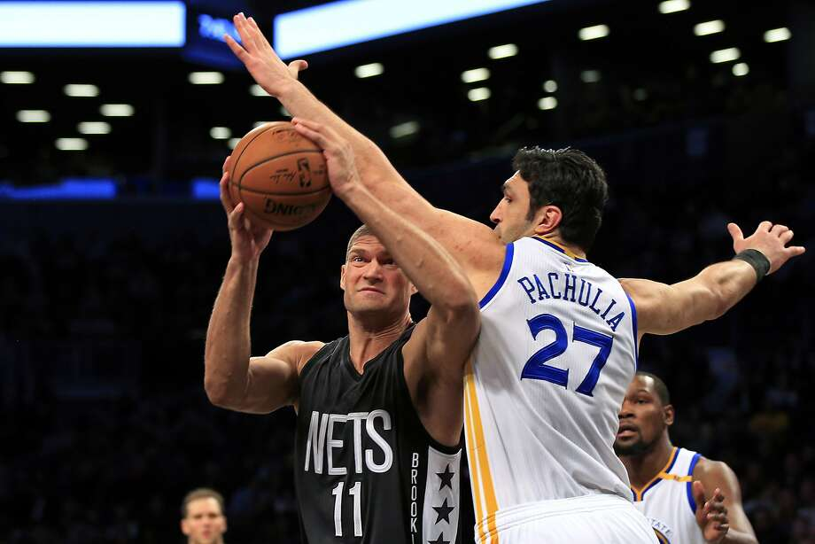 Zaza Pachulia offers resistance as Nets center Brook Lopez drives to the basket in the first half. Photo: Adam Hunger, Associated Press