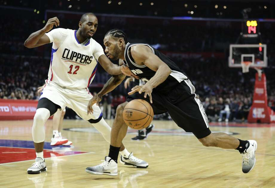 San Antonio Spurs' Kawhi Leonard, center, drives under pressure from Los Angeles Clippers' Luc Richard Mbah a Moute during the first half of an NBA basketball game Thursday, Dec. 22, 2016, in Los Angeles. (AP Photo/Jae C. Hong) Photo: Jae C. Hong/Associated Press