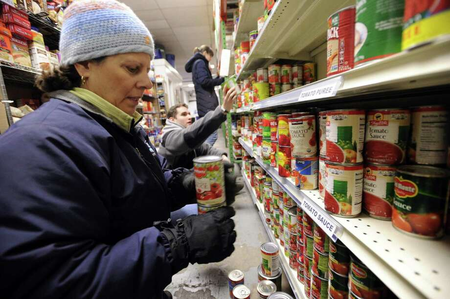 Maria Santanna, a CFO with Nestle Readyfresh Division, checks expiration dates and sorts canned goods along with a couple dozen company volunteers at the Food Bank of Lower Fairfield County in Stamford on Dec. 16, 2016. Photo: Matthew Brown / Hearst Connecticut Media / Stamford Advocate