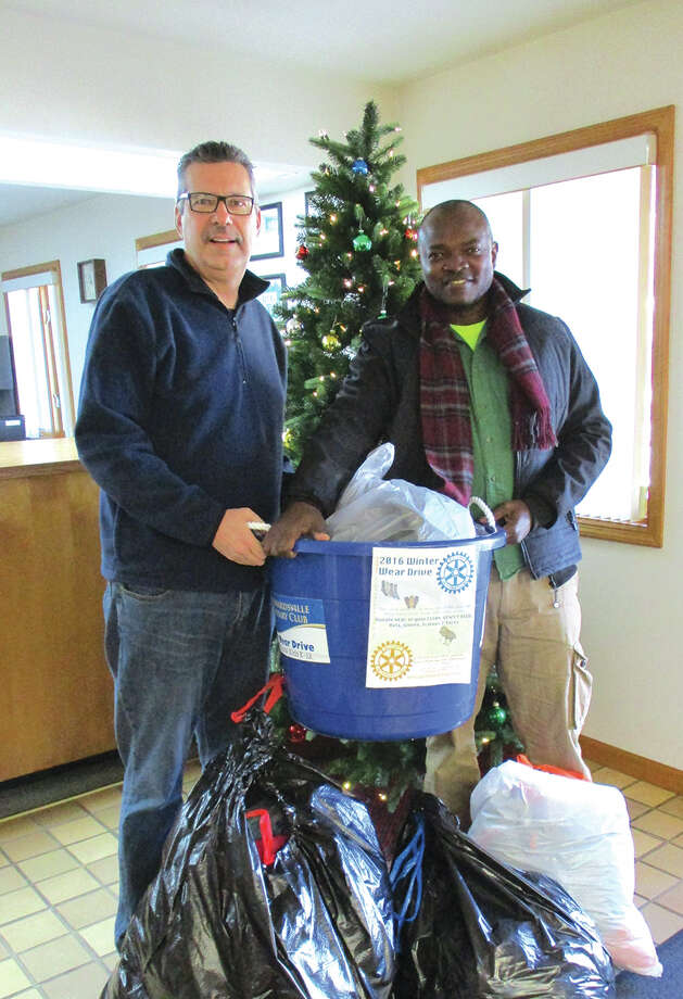 Members of the Edwardsville Rotary Club recently completed their annual Winter Wear Warm Up to benefit families in the school district. With the help of the Edwardsville Township and the Southern Illinois Girl Scouts, Rotarians Frank Miles (L) and Musonda Kapatamoyo delivered 10 tubs of new and gently used clothing to families in need. Photo: For The Intelligencer