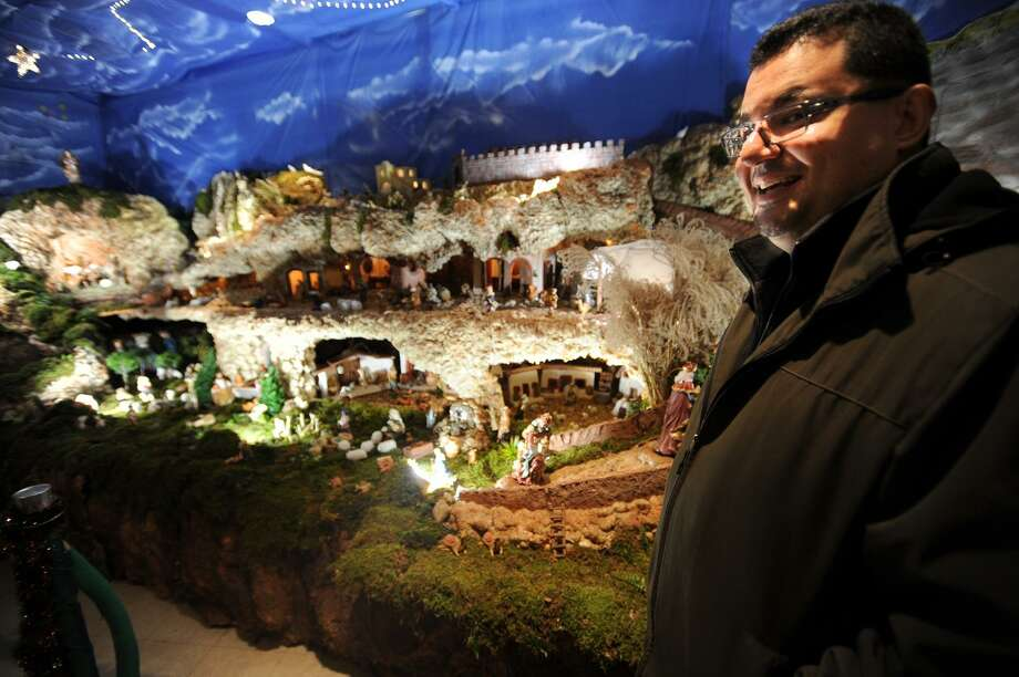 Father Rolando Torres shows off the wall to wall recreation of the Town of Bethlehem and manger scene at St. Mary Parish Roman Catholic Church on Sherman Street in Bridgeport, Conn. on Wednesday, December 21, 2016. The large displays are popular in South American homes and businesses as part of the Christmas tradition. Photo: Brian A. Pounds / Hearst Connecticut Media / Connecticut Post
