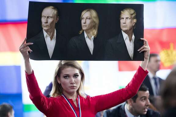 A journalist holds a poster with portraits of Russian President Vladimir Putin, left, France's far-right National Front president Marine Le Pen, center, and President-elect Donald Trump prior to Russian President's annual news conference in Moscow, Russia, Friday, Dec. 23, 2016. (AP Photo/Pavel Golovkin)