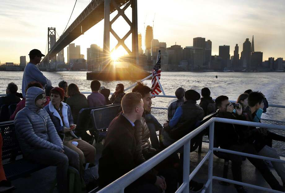 Harrison Dimmig and Pitichoke Chulapamornsri, center, sit on the top deck of the San Francisco to Alameda ferry Dec. 22, 2016 in San Francisco, Calif. Photo: Leah Millis, The Chronicle
