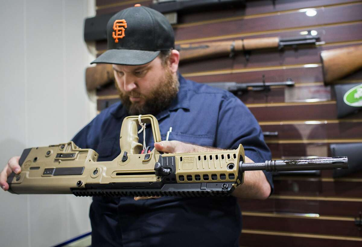 Todd Suttergren, CEO of Sutterarms, helps a customer with the delivery of his IWI Tavor X95 rifle, an Israeli firearm, Friday, Dec. 15, 2016 in Walnut Creek, CA.