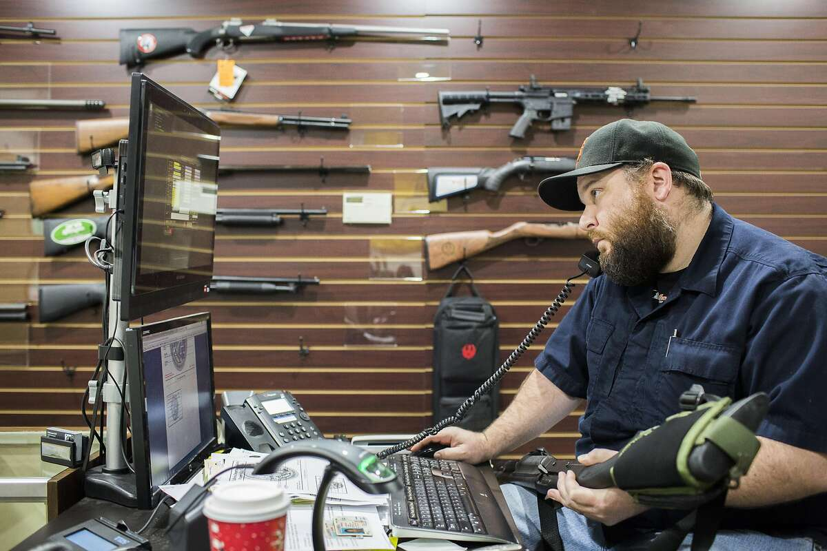 Todd Suttergren, CEO of Sutterarms, helps two customers transfer ownership of a Benelli M1 12 gauge shotgun, Friday, Dec. 15, 2016 in Walnut Creek, CA. The customers cancelled the exchange when they learned there would be a ten-day waiting period, deciding instead to make the transaction in Sacramento, where the buyer lives.