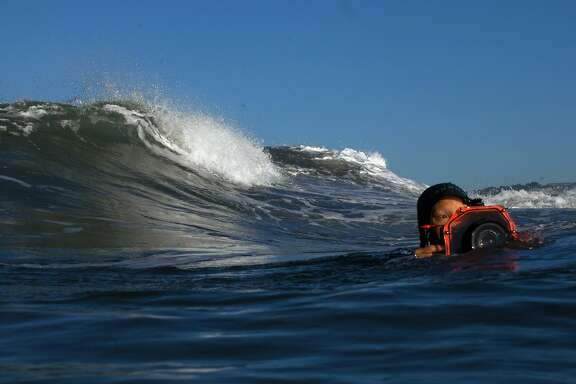 Sachi Cunningham swims off of ocean beach with her camera and surf housing Thursday morning, December 1, 2016 at Ocean Beach in San Francisco, Calif. Cunningham is a San Francisco-based surfer, filmmaker and photographer.  Brian Feulner, Special to the Chronicle