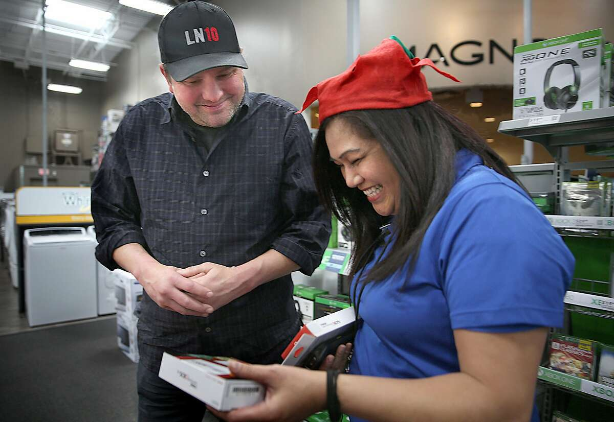 Billy Franchey (left) is told by sales staff Nia Marie Ripley that they have some Nintendo 3DS XL at Best Buy which he was searching for his 8 year old daughter Avery on Wednesday, December 21, 2016, in San Francisco, Calif. He had looked earlier at Target where they were out of stock.