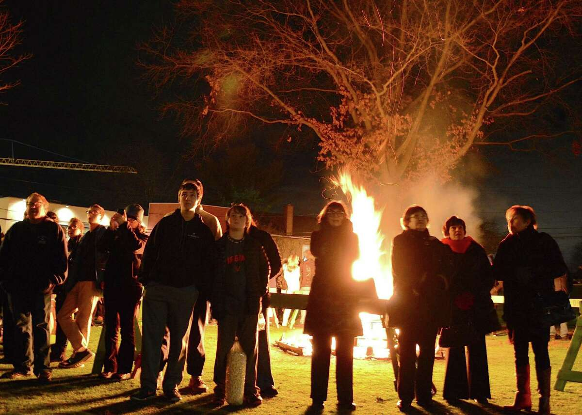 Spectators gathered around a bonfire on Jesup Green for First Night Westport on New Year's Eve 2016 look skyward at the fireworks display over the Saugatuck River.