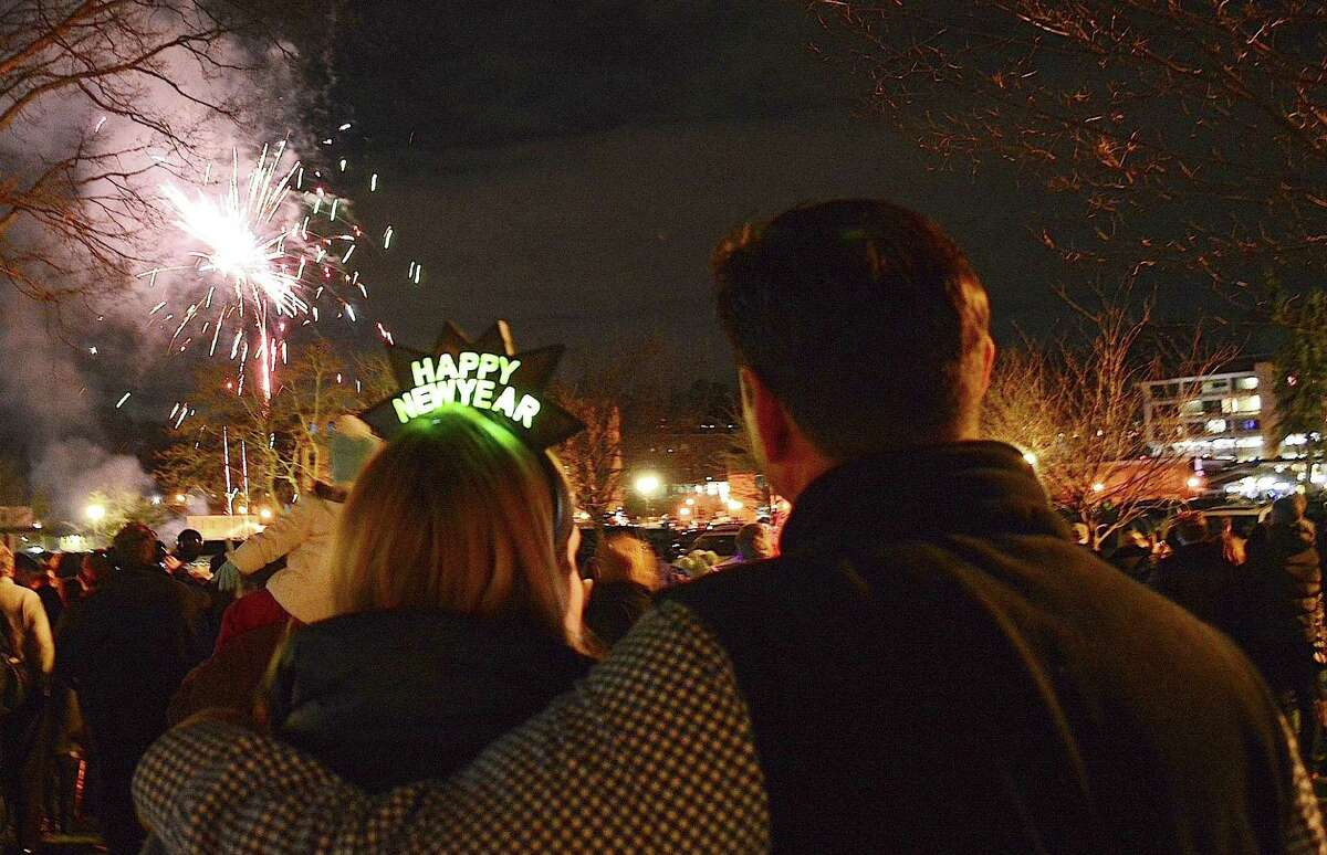 A couple welcomes 2016 watching fireworks over the Saugatuck River downtown on New Year's Eve, part of the annual First Night Westport celebration.