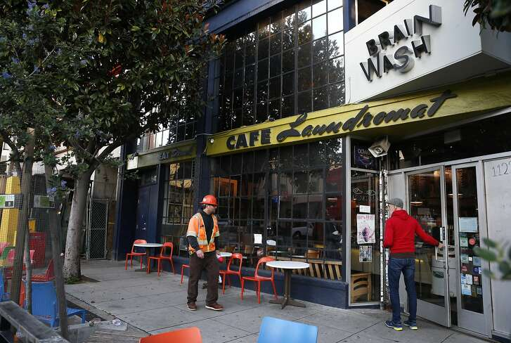 A construction worker passes the Brainwash cafe and laundromat in San Francisco, Calif. on Friday, Dec. 16, 2016. Owner Jeff Zalles has noticed a dramatic drop in business ever since a large residential development currently under construction broke ground next door to the Brainwash and is concerned he may have to shut down.