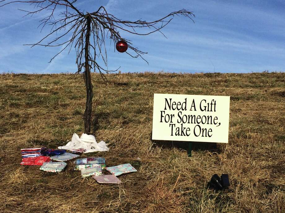 """A mystery """"giving tree"""" has popped up in Edwardsville. The tree, decorated with one lone ornament, is on the north side of Governors' Parkway east of Goshen Elementary School. Charitable citizens have placed presents under the tree for those in need. Photo: John Sommerhof • Intelligencer"""