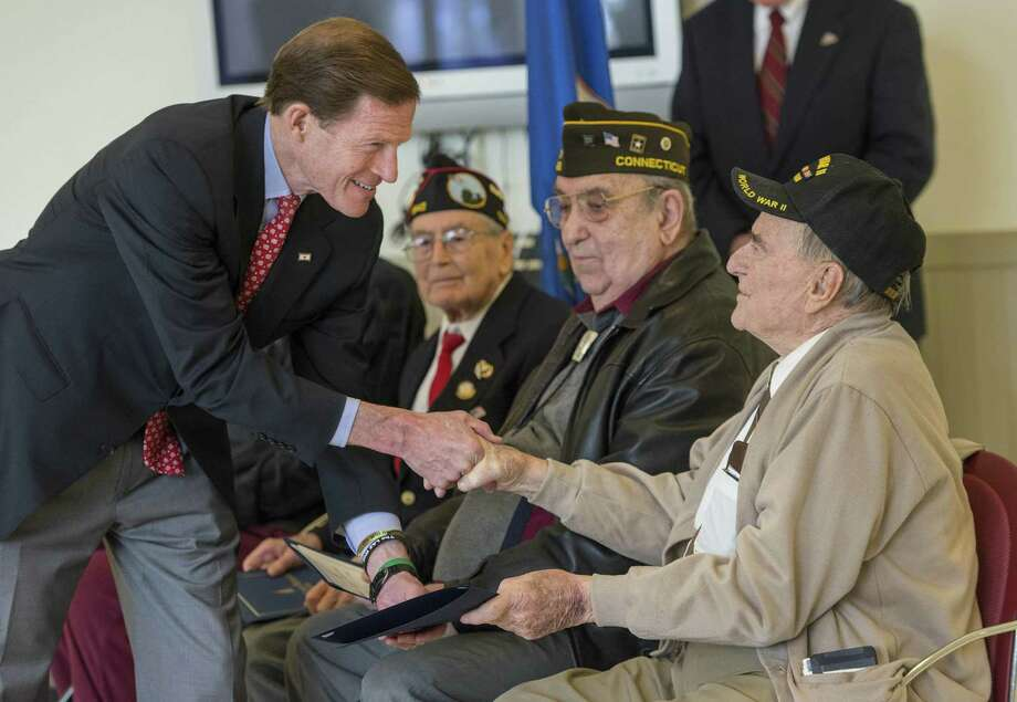 United States Senator Richard Blumenthal hands a Certificate of Special Recognition to LeRoy Glover who was being honored along with other World War II veterans at the Connecticut Fallen Heroes Foundations World War II Living Heroes Tribute held at the Monroe Town Senior Citizen Center in March. Photo: Mark Conrad / For Hearst Connecticut Media / Connecticut Post Freelance