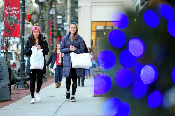 Teresa Andres, left, and her friend Julia Eustice, both of Fairfield, do some of their last minute Christmas shopping in downtown Fairfield, Conn., on Friday Dec. 23, 2016.