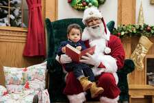 Larry Jefferson, playing the role of Santa, poses for a photo with Kingston Strong, of Minneapolis, at the Santa Experience at Mall of America in Bloomington, Minn. The nation's largest mall is hosting its first-ever black Santa Claus this weekend.