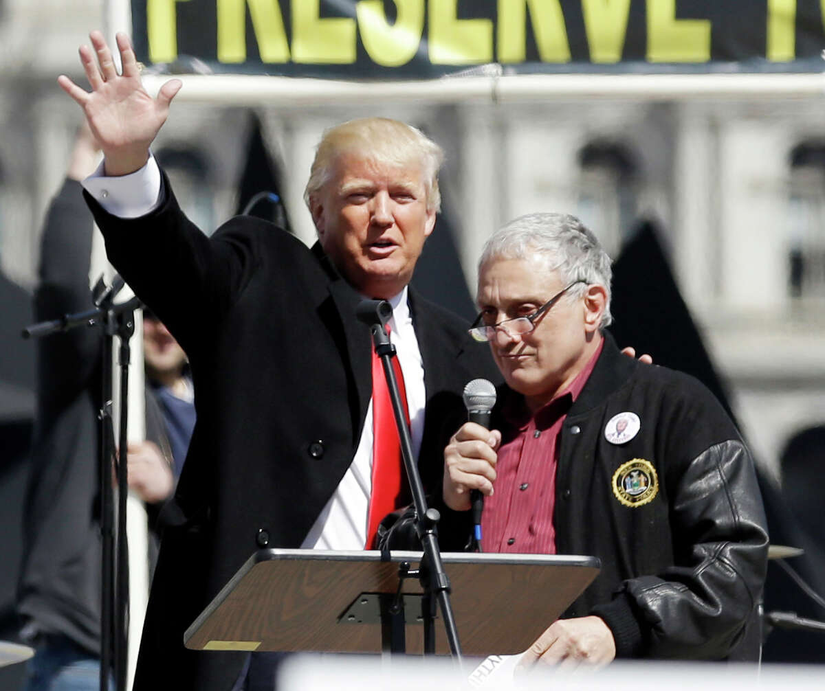 """FILE - In this April 1, 2014, file photo, Donald Trump, left, is joined by Carl Paladino during a gun rights rally at the Empire State Plaza in Albany, N.Y. Paladino, who co-chaired president-Elect Donald Trump's state campaign, confirmed to The Associated Press on Friday, Dec. 23, 3016 that he told a New York alternative newspaper he hoped President Barack Obama would die from mad cow disease and that the first lady would """"return to being a male."""" (AP Photo/Mike Groll, File) ORG XMIT: NYR101"""