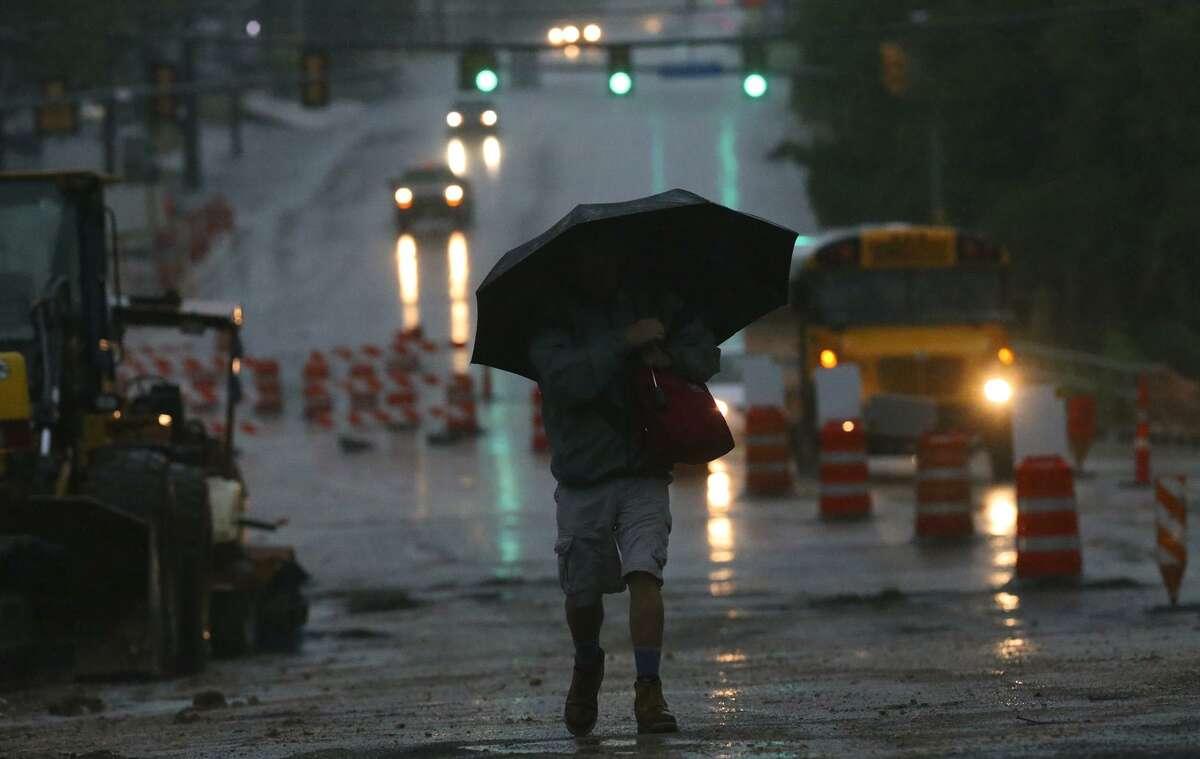Chris Walton trudges through the rain on West Avenue near the intersection of Nakoma.