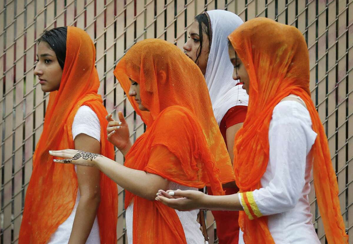 """Rain falls on several young Sikh women as they join other members of the Sikh community from across the state for a march in downtown San Antonio on Saturday, May 14, 2016. According to officials at the event about 1,000 Sikhs gathered for food, fellowship, worship and public awareness. Despite a burst of rain showers prior to the start of the march, organizers and participants still went ahead with the event. """"We want people to know that the Sikh community shares those American values of equality and justice for all,"""" said Simran Kaur of the Sikh Center of San Antonio. """"The majority of the people you see wearing turbans are actually Sikh Americans and the turban represents the tenants of our faith which are justice for all and equality. Our community is very open and willing to engage. Our house of worship is open to all,"""" Kaur said. This year marks nearly 10 years that the local Sikh community has held a march for public awareness according to Kaur. (Kin Man Hui/San Antonio Express-News)"""