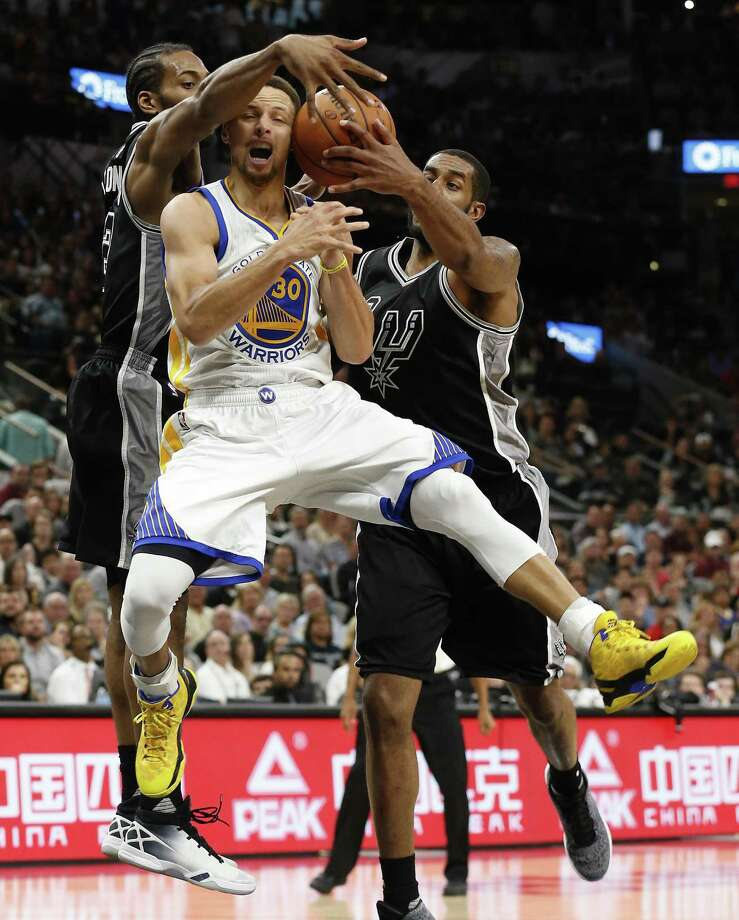 Spurs' Kawhi Leonard (02) and LaMarcus Aldridge (12) defend against Golden State Warriors' Stephen Curry (30) at the AT&T Center on Sunday, Apr. 10, 2016. The Warriors defeated the Spurs, 92-86. The Warriors with the victory also tied the 1995-96 Chicago Bulls for most wins in an NBA season with 72 victories. (Kin Man Hui/San Antonio Express-News) Photo: Kin Man Hui, Staff / San Antonio Express-News / ©2016 San Antonio Express-News