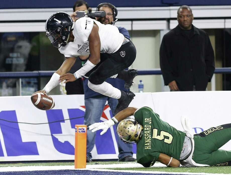 Steele quarterback Xavier Martin (01) leaps over DeSoto's Byron Hanspard (05) for a score late in the game in the Class 6A Division II state championship football game at AT&T Stadium in Arlington on Saturday, Dec. 17, 2016. DeSoto defeated Steele, 39-29. (Kin Man Hui/San Antonio Express-News) Photo: Kin Man Hui, Staff / San Antonio Express-News / ©2016 San Antonio Express-News