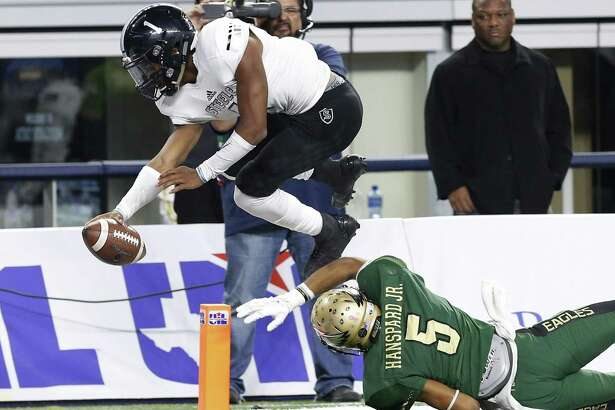 Steele quarterback Xavier Martin (01) leaps over DeSoto's Byron Hanspard (05) for a score late in the game in the Class 6A Division II state championship football game at AT&T Stadium in Arlington on Saturday, Dec. 17, 2016. DeSoto defeated Steele, 39-29. (Kin Man Hui/San Antonio Express-News)