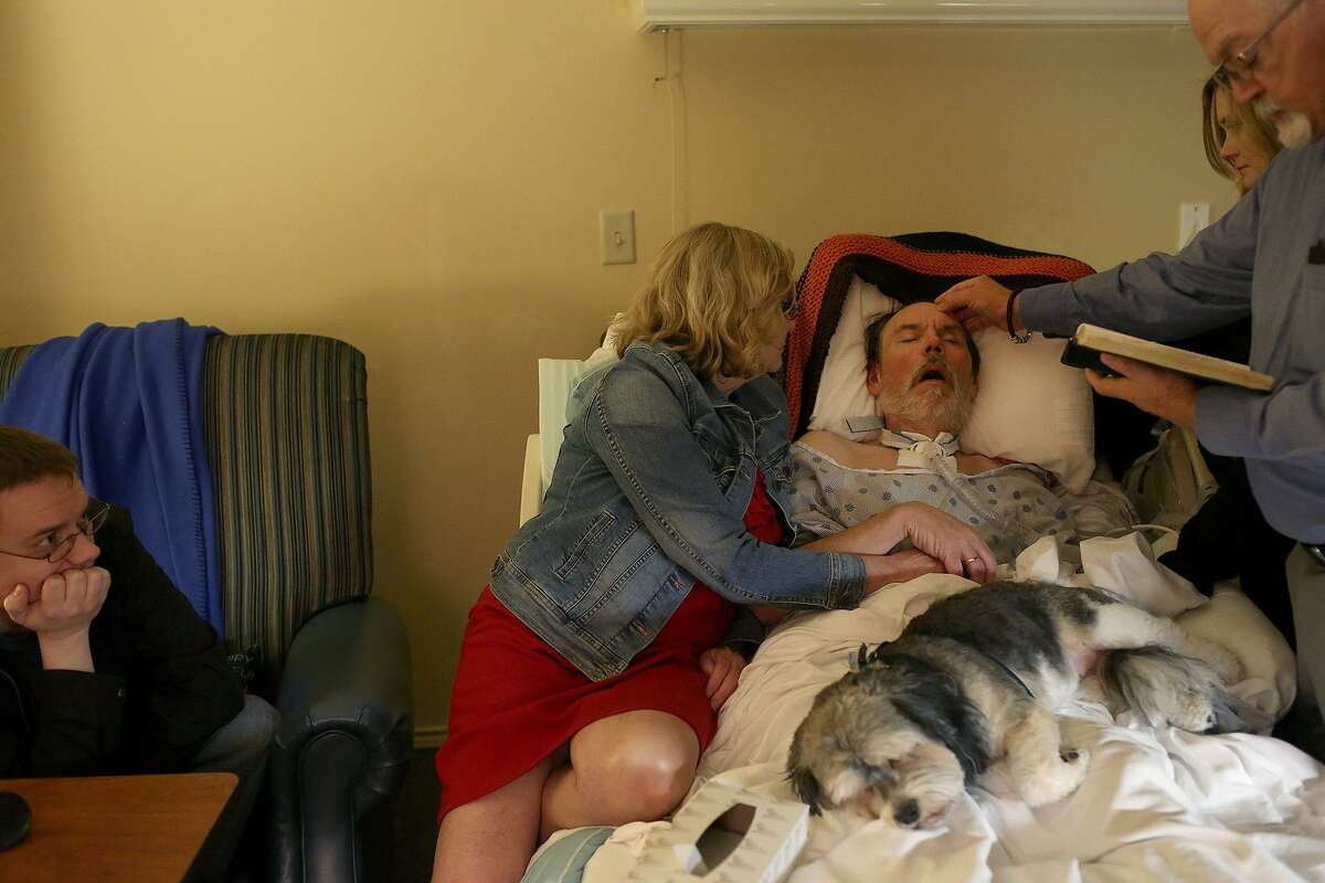 """With a family dog sleeping on his lap, Walt receives Last Rites from the Rev. Chuck Woehler. The pastor assured Walt that his family was """"well and strong,"""" and that he could let go, if he was ready."""
