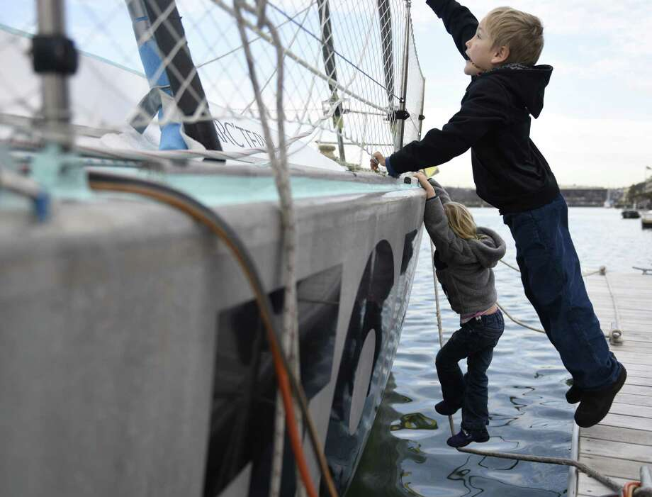 Noe Schwörer, 7, jumps and Alegra Schwörer, 5, climbs onto their family's 50-foot sailboat docked at Indian Harbor Yacht Club in Greenwich, Conn. Thursday, Dec. 22, 2016. Climatologist Dario Schwörer, his wife Sabine and their five children are the leaders of the TOPtoTOP Global Climate Expedition, which has circumnavigated the globe conducting field-based research, visiting remote regions and sharing solutions to protect and preserve the planet from climate change. The family is making a two-week stop in Greenwich to speak to locals about their mission before heading off to sea again after the New Year. Photo: Tyler Sizemore / Hearst Connecticut Media / Greenwich Time