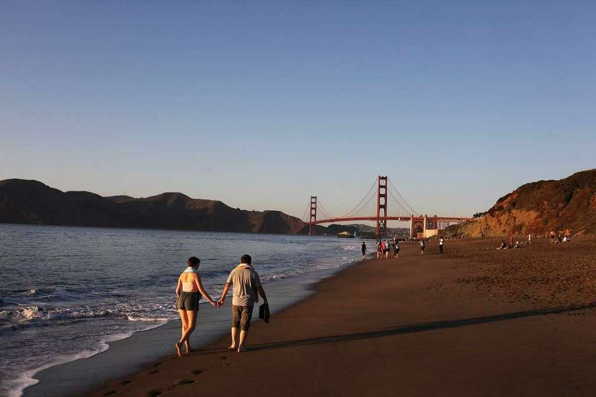 Police identified the woman who drowned in Baker Beach Thursday as a 40-year-old woman from Rhode Island. Kelly Martin and Robert Da Silva (l-r) walk on Baker Beach just before sunset on October 5, 2013 in San Francisco. On Thursday afternoon, a woman drowned in the waters off the beach in the Presidio, officials said.