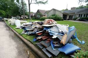 A pile of wet carpeting and sheetrock sits outside a house in the Hearthstone subdivision of Copperfield after water from nearby Horsepen Creek spilled out in April 2016, flooding several homes.