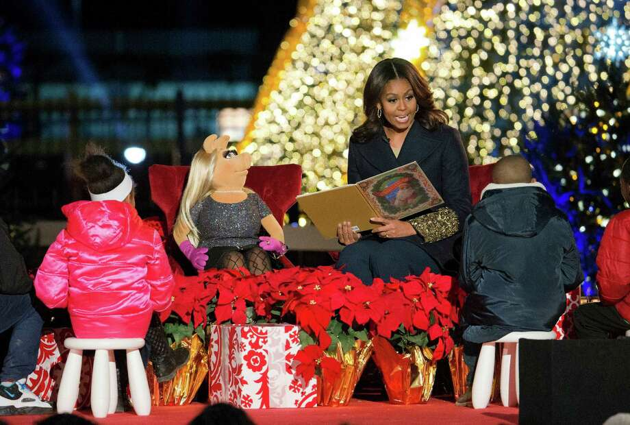 FILE - In this Dec. 3, 2015, file photo, first lady Michelle Obama with Miss Piggy, left, read 'Twas the Night Before Christmas for children on stage during the National Christmas Tree Lighting ceremony at the Ellipse in Washington. When Michelle Obama considered the daunting prospect of becoming first lady, she purposely avoided turning to books by her predecessors for guidance. Instead, she turned inward. (AP Photo/Pablo Martinez Monsivais) ORG XMIT: WX420 Photo: Pablo Martinez Monsivais / Copyright 2016 The Associated Press. All rights reserved.