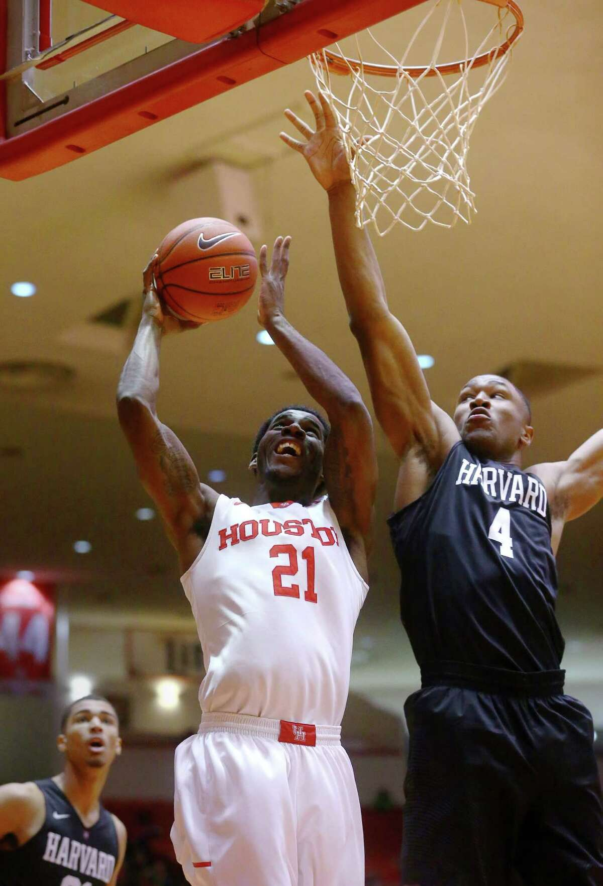 Houston Cougars guard Damyean Dotson (21) drives to the basket while guarded by Harvard Crimson forward Zena Edosomwan (4) during the first half of an NCAA basketball game at Hofheinz Pavilion, Friday, Dec. 23, 2016, in Houston.