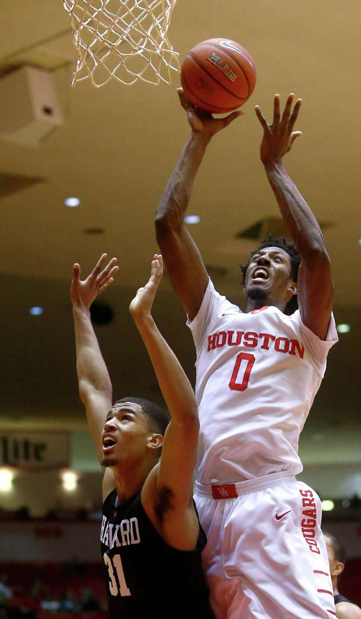 Houston Cougars forward Danrad Knowles (0) drives to the basket over Harvard Crimson forward Seth Towns (31)\during the first half of an NCAA basketball game at Hofheinz Pavilion, Friday, Dec. 23, 2016, in Houston.