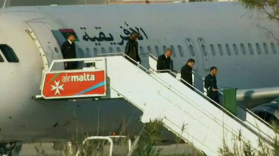 An Afriqiyah Airways plane stands on the tarmac at Malta International airport as people depart, Friday, Dec. 23, 2016. Hijackers diverted the Libyan commercial plane to Malta on Friday and threatened to blow it up with hand grenades, Maltese authorities and state media said. (TVM via AP) ORG XMIT: NY112 / TVM