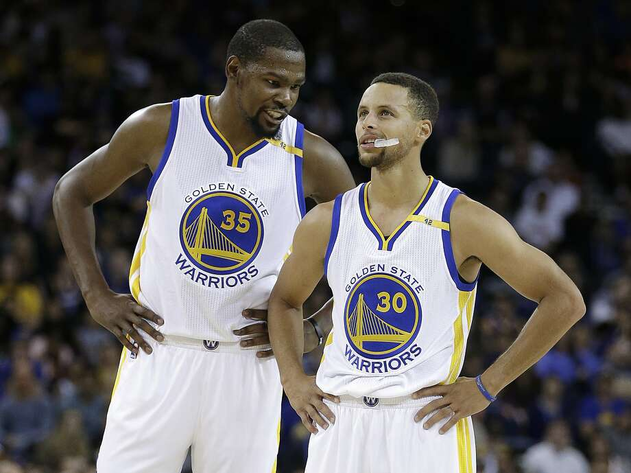 FILE - In this Oct. 4, 2016, file photo, Golden State Warriors' Kevin Durant, left, speaks with Stephen Curry (30) during the first half of a pre-season NBA basketball game against the Los Angeles Clippers in Oakland, Calif. For everyone who questioned whether Stephen Curry and Kevin Durant could coexist and put their egos aside for the greater good, the Golden State Warriors are a couple of months into the season and the superstars are thriving together. (AP Photo/Ben Margot) Photo: Ben Margot, Associated Press