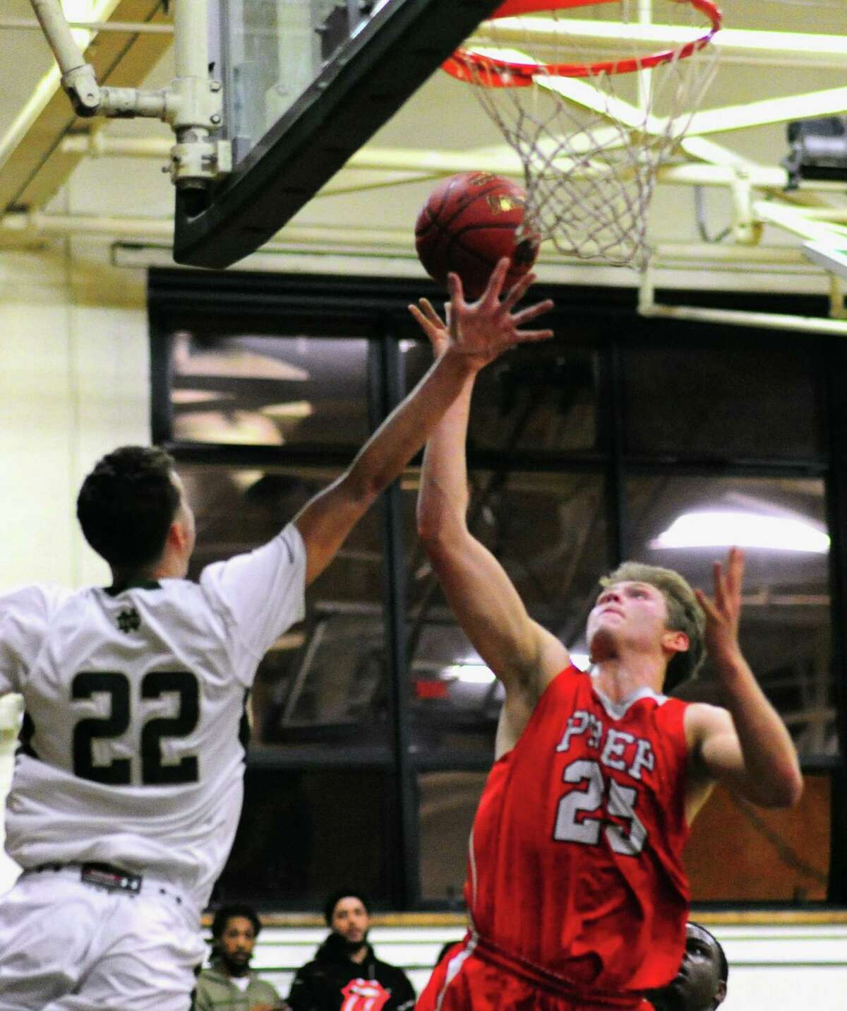 Fairfield Prep's Patrick Harding lays up the ball as Notre Dame of West Haven's Connor Raines defends, during boys high school basketball action in West Haven, Conn., on Friday December 23, 2016.