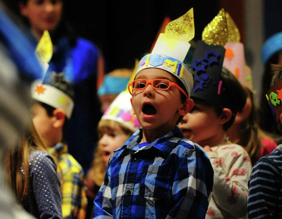 Above, Eli Pollock, 4, sings during Congregation B'nai Israel's annual Bonim Preschool Hanukkah Show in Bridgeport on Wednesday. The show, led by Cantor Sheri Blum, the show featured musical selections sung by children from pre-kindergarten ages 2 to 6. After the show, latkes, salad, jelly donuts, and potluck style dinner was served. Photo: Christian Abraham / Hearst Connecticut Media / Connecticut Post