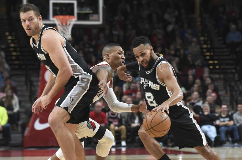San Antonio Spurs guard Patty Mills drives to the basket around a pick set by forward David Lee as Portland Trail Blazers guard Damian Lillard defends during the first half of an NBA basketball game in Portland, Ore., Friday, Dec. 23, 2016. AP Photo/Steve Dykes) Photo: Steve Dykes/Associated Press