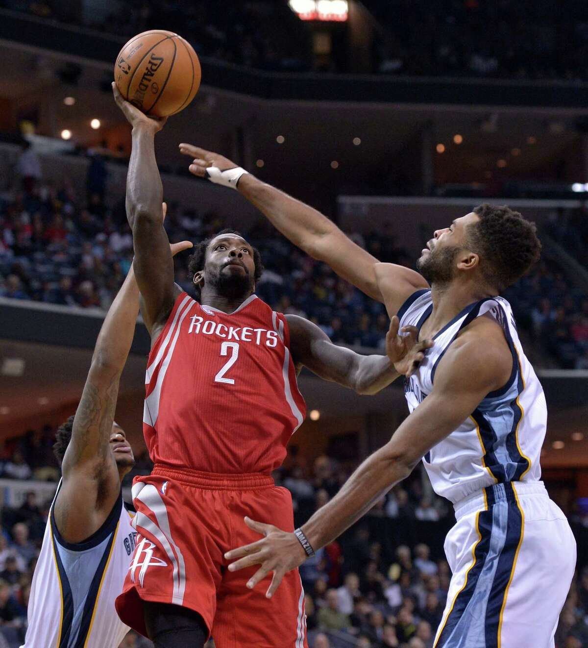 Rockets guard Pat Beverley, left, drives between two Grizzlies to the basket. He finished with 13 points.